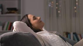Γυναίκα που αφήνει το τηλέφωνο και που χαλαρώνει σε έναν καναπέ στη νύχτα φιλμ μικρού μήκους