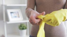Γυναίκα που βάζει στα λαστιχένια γάντια για τα οικιακά φιλμ μικρού μήκους
