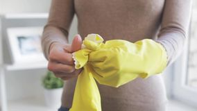 Γυναίκα που βάζει στα λαστιχένια γάντια για τα οικιακά απόθεμα βίντεο