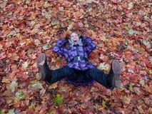Γυναίκα που βάζει στα φύλλα ευτυχή στοκ εικόνα με δικαίωμα ελεύθερης χρήσης