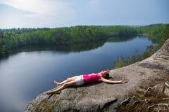 Γυναίκα που βάζει στον απότομο βράχο μια χαλάρωση επάνω από τη λίμνη Yastrebinoye, περιοχή Priozersky στην περιοχή του Λένινγκραν Στοκ φωτογραφίες με δικαίωμα ελεύθερης χρήσης