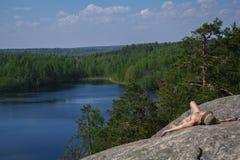 Γυναίκα που βάζει στον απότομο βράχο μια χαλάρωση επάνω από τη λίμνη Yastrebinoye, περιοχή Priozersky στην περιοχή του Λένινγκραν Στοκ Εικόνες