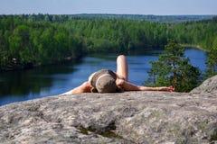 Γυναίκα που βάζει στον απότομο βράχο μια χαλάρωση επάνω από τη λίμνη Yastrebinoye, περιοχή Priozersky στην περιοχή του Λένινγκραν Στοκ φωτογραφία με δικαίωμα ελεύθερης χρήσης