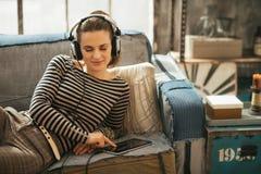Γυναίκα που βάζει στον καναπέ και τη μουσική ακούσματος Στοκ εικόνα με δικαίωμα ελεύθερης χρήσης