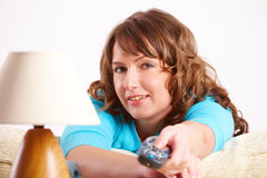 Γυναίκα που βάζει στον καναπέ με τον απομακρυσμένο ελεγκτή Στοκ Εικόνες