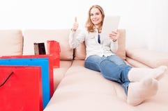 Γυναίκα που βάζει στο chouch με την ταμπλέτα που παρουσιάζει όπως Στοκ φωτογραφίες με δικαίωμα ελεύθερης χρήσης