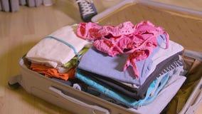 Γυναίκα που βάζει τα πράγματα και τα ενδύματα στη βαλίτσα ταξιδιού στο πάτωμα στο εγχώριο δωμάτιο φιλμ μικρού μήκους