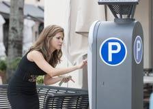 Γυναίκα που βάζει τα χρήματα σε έναν μετρητή χώρων στάθμευσης Στοκ φωτογραφία με δικαίωμα ελεύθερης χρήσης