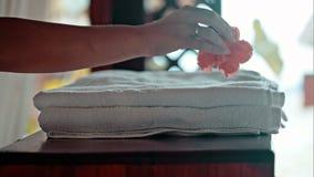 Γυναίκα που βάζει τις φρέσκες πετσέτες στον πίνακα και το λουλούδι απόθεμα βίντεο