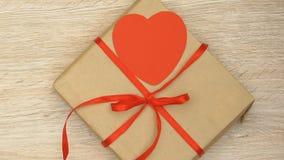 Γυναίκα που βάζει το κιβώτιο δώρων με την καρδιά στον πίνακα, ημέρα βαλεντίνων παρούσα για αγαπημένο απόθεμα βίντεο