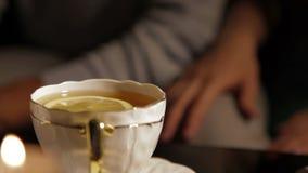 Γυναίκα που βάζει το λεμόνι στο τσάι Η αγαπώντας γυναίκα έβαλε το χέρι της στο γόνατό του απόθεμα βίντεο