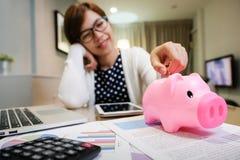 Γυναίκα που βάζει το νόμισμα στη ρόδινη τράπεζα Piggy στοκ εικόνες