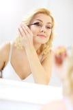 Γυναίκα που βάζει mascara στο λουτρό Στοκ εικόνες με δικαίωμα ελεύθερης χρήσης