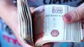 Γυναίκα που βγάζει φύλλα μέσω ενός πακέτου των ρωσικών τραπεζογραμματίων στις μετονομασίες 5000 ρουβλιών απόθεμα βίντεο