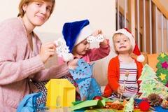 Γυναίκα που βοηθά τις κόρες για να κάνει τη διακόσμηση για τα Χριστούγεννα Στοκ Εικόνα
