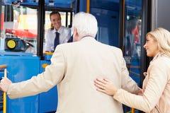 Γυναίκα που βοηθά τον ανώτερο άνδρα για να επιβιβαστεί στο λεωφορείο στοκ εικόνα