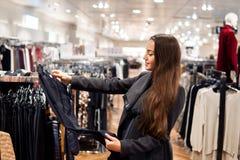 Γυναίκα που βρίσκεται νέα ενδύματα σε μια υπεραγορά καταστημάτων στοκ φωτογραφίες με δικαίωμα ελεύθερης χρήσης