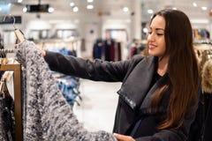 Γυναίκα που βρίσκεται νέα ενδύματα σε μια υπεραγορά καταστημάτων στοκ εικόνα