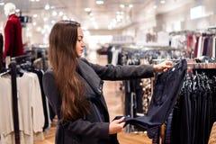 Γυναίκα που βρίσκεται νέα ενδύματα σε μια υπεραγορά καταστημάτων στοκ εικόνα με δικαίωμα ελεύθερης χρήσης