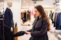 Γυναίκα που βρίσκεται νέα ενδύματα σε μια υπεραγορά καταστημάτων στοκ εικόνες