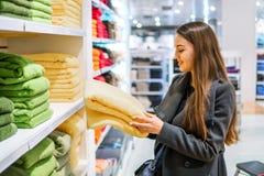 Γυναίκα που βρίσκεται νέες πετσέτες σε ένα κατάστημα υπεραγορών καταστημάτων στοκ εικόνα