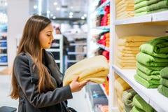 Γυναίκα που βρίσκεται νέες πετσέτες σε ένα κατάστημα υπεραγορών καταστημάτων στοκ φωτογραφία με δικαίωμα ελεύθερης χρήσης