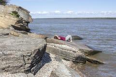Γυναίκα που βρίσκεται σε ένα μεγάλο δικαίωμα λίθων εκτός από τη λίμνη που απολαμβάνει τον ήλιο Στοκ Εικόνα