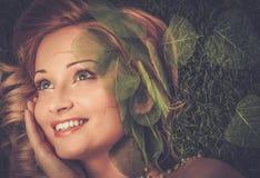 Γυναίκα που βρίσκεται σε μια φρέσκια χλόη άνοιξη Στοκ Φωτογραφίες