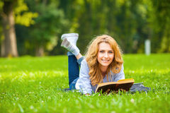 Γυναίκα που βρίσκεται στη χλόη και που διαβάζει ένα βιβλίο Στοκ φωτογραφίες με δικαίωμα ελεύθερης χρήσης