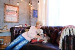 Γυναίκα που βρίσκεται στον καναπέ δίπλα στο σκυλί και που χαμογελά στη κάμερα ενάντια στο W Στοκ Εικόνα