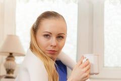 Γυναίκα που βρίσκεται στον καναπέ κάτω από το γενικό τσάι κατανάλωσης στοκ φωτογραφίες με δικαίωμα ελεύθερης χρήσης