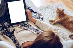 Γυναίκα που βρίσκεται στον καναπέ με την ταμπλέτα και τον καφέ υπό εξέταση Στοκ Εικόνες