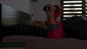 Γυναίκα που βρίσκεται στο κρεβάτι στο γυρίζοντας συναγερμό πρωινού μακριά στο έξυπνο τηλέφωνο και που ελέγχει το απόθεμα βίντεο