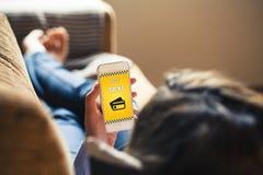 Γυναίκα που βρίσκεται στο σπίτι χρησιμοποιώντας ένα κινητό τηλέφωνο για να πληρώσει ένα ταξί Στοκ εικόνα με δικαίωμα ελεύθερης χρήσης