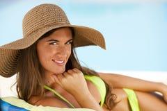Γυναίκα που βρίσκεται στο deckchair από swimming-pool στοκ φωτογραφία με δικαίωμα ελεύθερης χρήσης