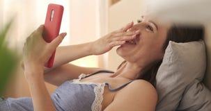 Γυναίκα που γελά κάνοντας την τηλεοπτική συνομιλία που χρησιμοποιεί το κινητό τηλέφωνο στο κρεβάτι απόθεμα βίντεο