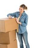 Γυναίκα που γράφει στα κουτιά από χαρτόνι στοκ φωτογραφία