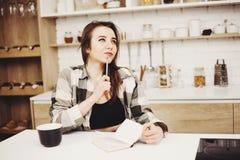 Γυναίκα που γράφει στον καφέ πρωινού κατανάλωσης ημερολογίων στοκ φωτογραφίες