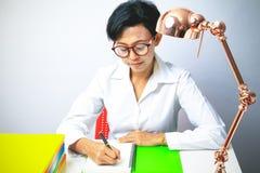 Γυναίκα που γράφει στο σπειροειδές σημειωματάριο που τοποθετείται στο φωτεινό υπολογιστή γραφείου Στοκ Εικόνες