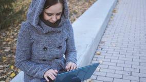 Γυναίκα που γράφει στο lap-top στον πάγκο πάρκων απόθεμα βίντεο