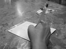 Γυναίκα που γράφει τη λαμβάνουσα διεύθυνση στον ταχυδρομώντας Μαύρο φακέλων και wh στοκ εικόνες