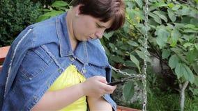Γυναίκα που γράφει sms στο κινητό τηλέφωνό σας φιλμ μικρού μήκους