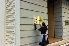 Γυναίκα που γυαλίζει ένα σημάδι εστιατορίων στοκ φωτογραφία