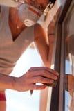 Γυναίκα που γυαλίζει ένα παράθυρο με την άμμο Στοκ Φωτογραφίες