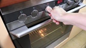 Γυναίκα που γυρίζει, που ανάβει τη σόμπα, που ψήνει το φούρνο και που αλλάζει τους τρόπους προκειμένου να προθερμανθεί και να μαγ φιλμ μικρού μήκους