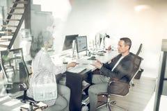 Γυναίκα που δίνει το βιογραφικό σημείωμά της στον επιχειρηματία ενώ έχοντας τη συνέντευξη εργασίας στοκ φωτογραφίες