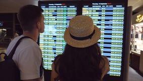 Γυναίκα που δείχνει κάτι το φίλο του στην οθόνη πινάκων χρονοδιαγράμματος Νέο ζεύγος που εξετάζει το πρόγραμμα πτήσης στον αερολι απόθεμα βίντεο