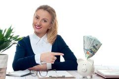 Γυναίκα που δείχνει τη piggy τράπεζα με τη δέσμη των τραπεζογραμματίων χρημάτων Στοκ εικόνα με δικαίωμα ελεύθερης χρήσης
