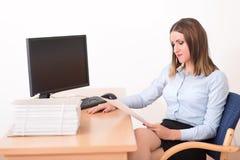 Γυναίκα που διαβάζει ένα έγγραφο στο γραφείο Στοκ εικόνα με δικαίωμα ελεύθερης χρήσης