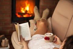 Γυναίκα που διαβάζει ένα βιβλίο και που απολαμβάνεται μια καυτή σοκολάτα από την πυρκαγιά Στοκ Εικόνες